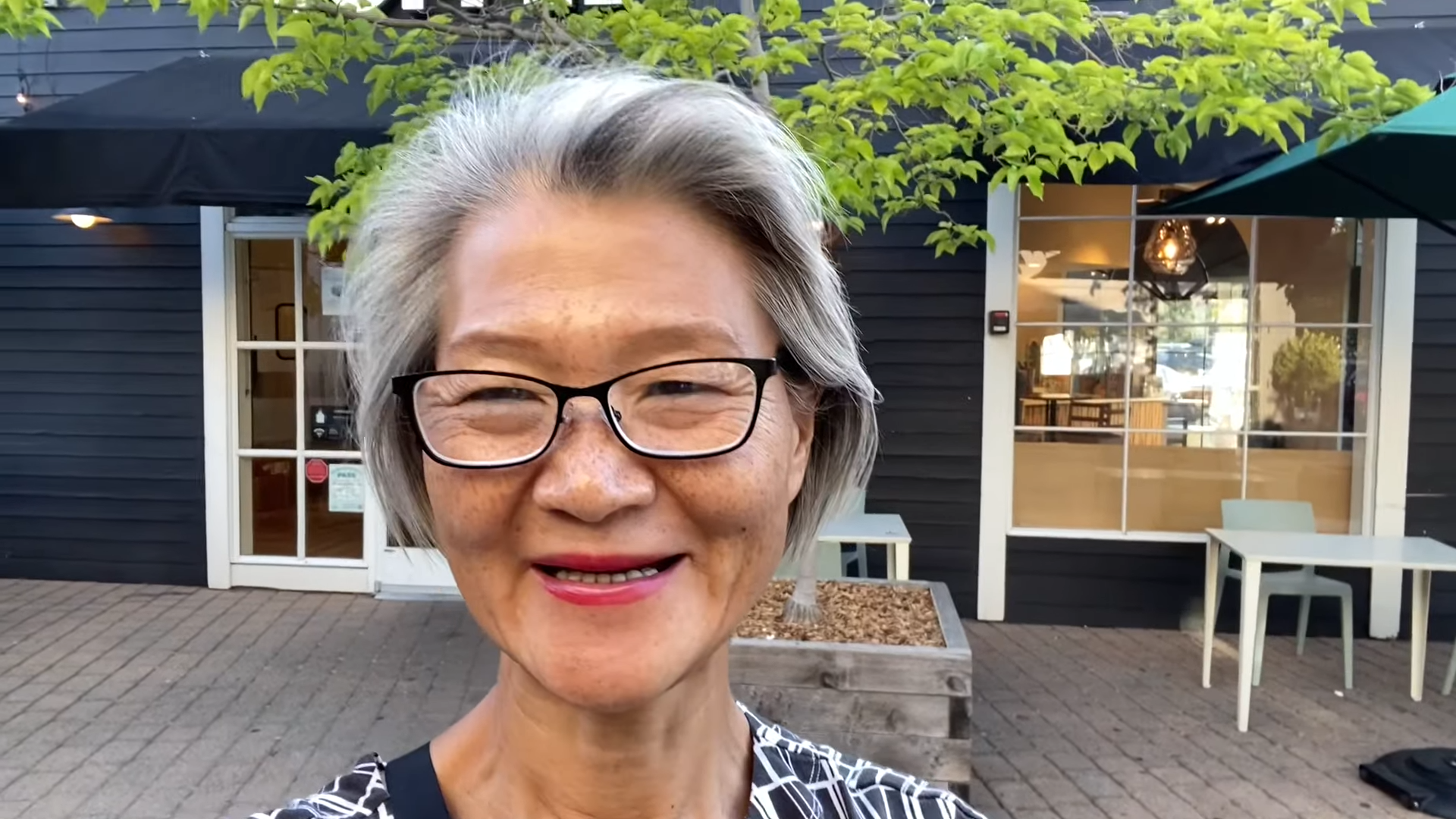 woman wearing glasses standing in front of a building and smiling