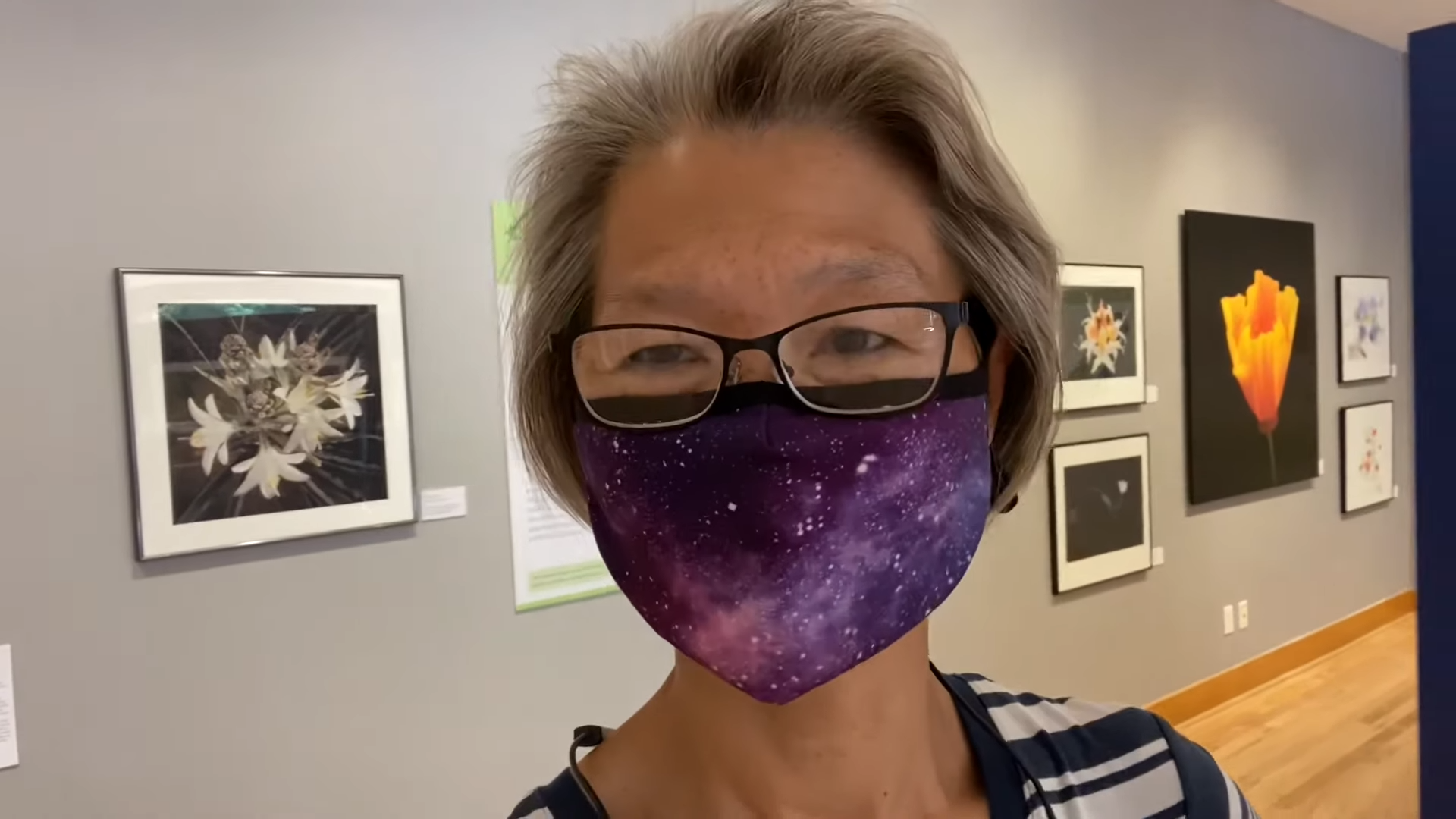 woman wearing glasses and a purple mask in front of artwork at a museum
